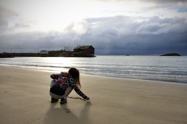 Menina criança sentada em uma costa, senja, noruega