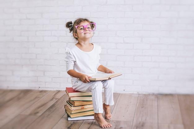 Menina criança sentada em uma pilha de livros com óculos