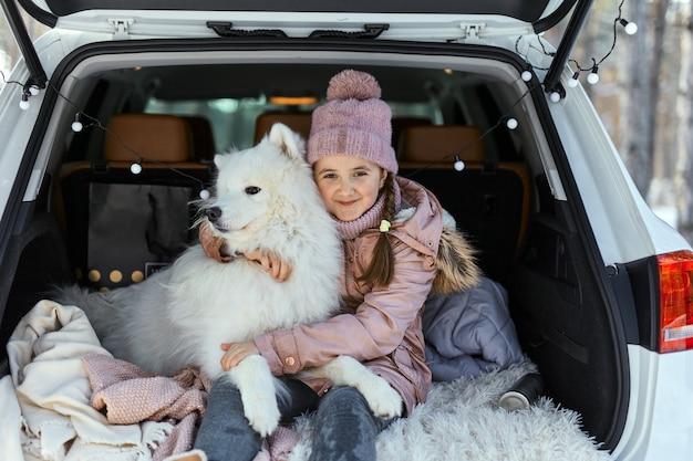 Menina criança sentada no porta-malas do carro com seu animal de estimação, um cachorro branco samoieda, no inverno