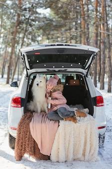 Menina criança sentada no porta-malas do carro com seu animal de estimação, um cachorro branco samoieda
