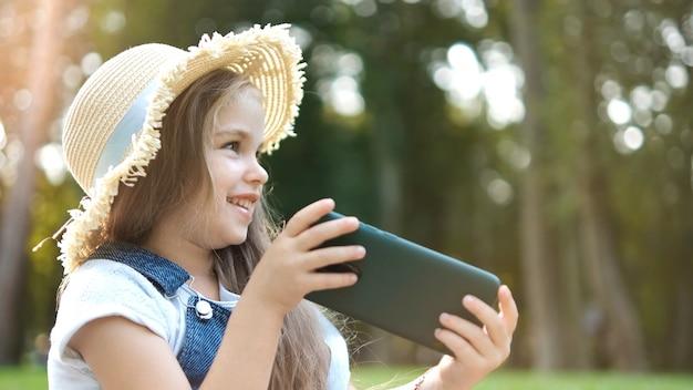 Menina criança sorridente feliz assistindo em seu telefone móvel ao ar livre no verão.