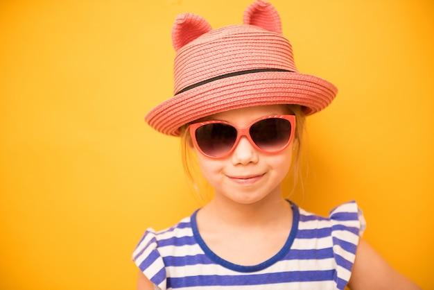 Menina criança sorridente no chapéu com orelhas e óculos de sol amarelo