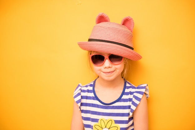 Menina criança sorridente no chapéu com orelhas e óculos de sol
