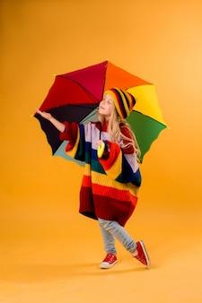 Menina criança sorrindo em um suéter multicolorido brilhante e chapéu segurando um guarda-chuva fica em um espaço amarelo