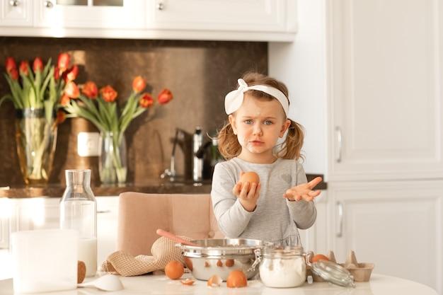 Menina criança surpresa com farinha no rosto pronta para cozinhar bolo para a festa de páscoa em uma cozinha branca e ensolarada com flores da primavera