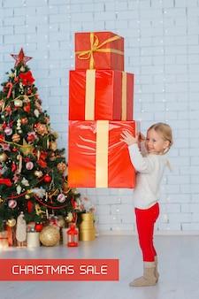 Menina criança tem uma torre de caixas de presente vermelha nas mãos