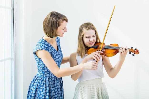 Menina criança tocando violino está envolvida com a professora linda e feliz na sala branca com uma janela