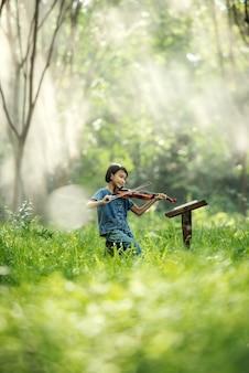 Menina criança tocando violino para estudar na tailândia
