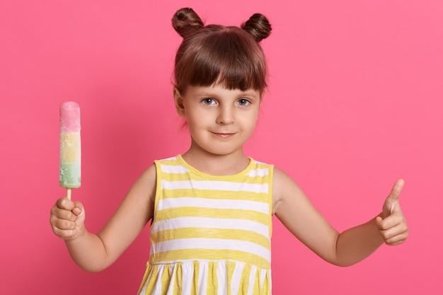 Menina criança tomando sorvete, parece feliz e mostra o polegar