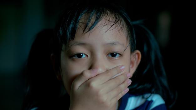Menina criança triste cobrindo a boca com as mãos no quarto escuro.