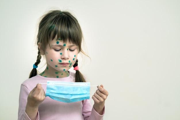Menina criança vestindo azul máscara médica protetora doente com varicela, sarampo ou vírus da rubéola com erupções no corpo. proteção infantil durante epidemia de coronovírus. conceito de contágio covid-19.