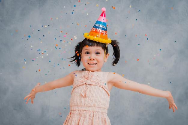 Menina criança vomita alegremente enfeites e enfeites coloridos.