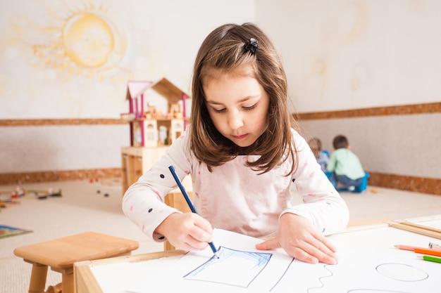Menina criativa desenhando uma imagem com lápis azuis