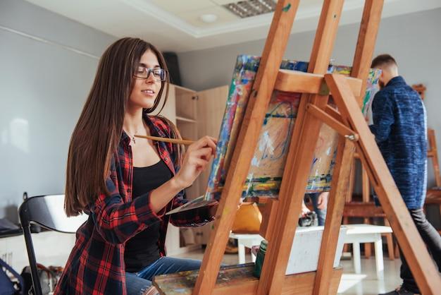 Menina criativa pintor pensativo pinta uma imagem colorida na lona com cores de óleo na oficina.