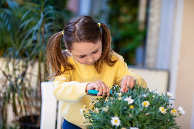 Menina cuidando das flores da varanda, podando com tesouras de poda.