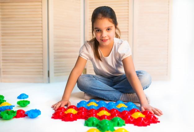 Menina curiosa coloca quebra-cabeças de plástico