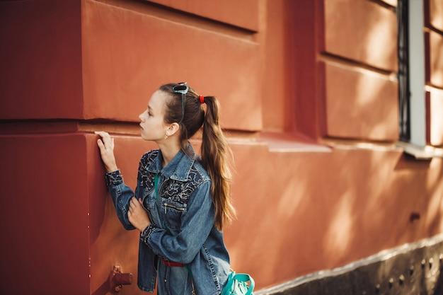 Menina curiosa em roupas jeans fica perto de um antigo prédio bonito restaurado.