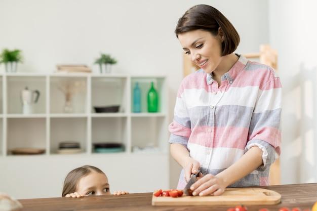 Menina curiosa que espreita para fora da mesa da cozinha enquanto vê sua mãe cortando tomates frescos para salada