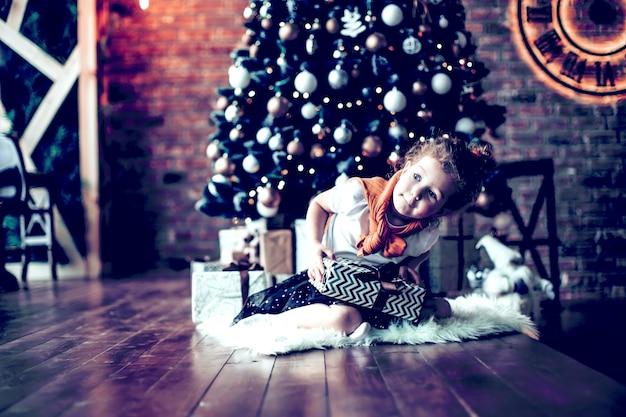 Menina curiosa sentada perto da árvore de natal. o conceito de natal