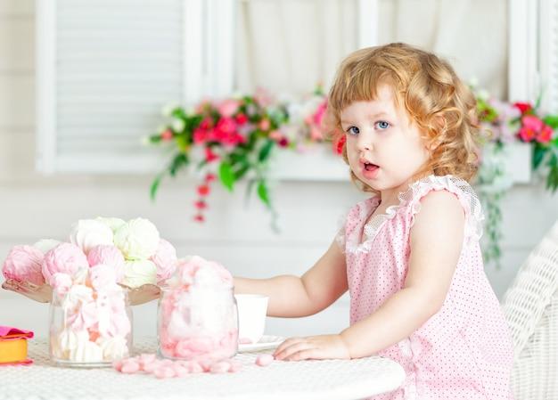 Menina curly bonito pequena em um vestido cor-de-rosa com laço e às bolinhas que sentam-se na tabela e que comem doces diferentes.