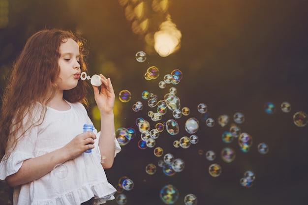 Menina curly soprando bolhas de sabão.