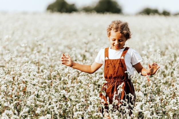 Menina curtindo o dia em um campo de trigo