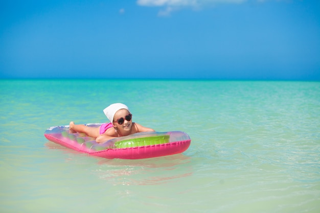 Menina cute sunbathing na cama-de-rosa no mar quente