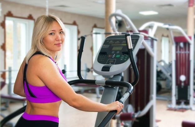 Menina da aptidão que exercita no equipamento do gym da escada rolante do moonwalker.