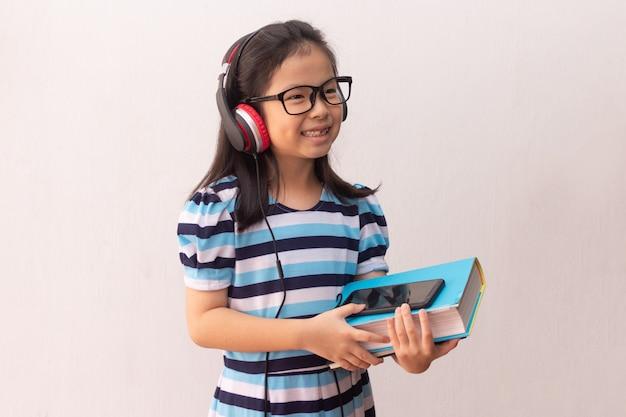 Menina da ásia com fones de ouvido, ouvindo música e segurando livros