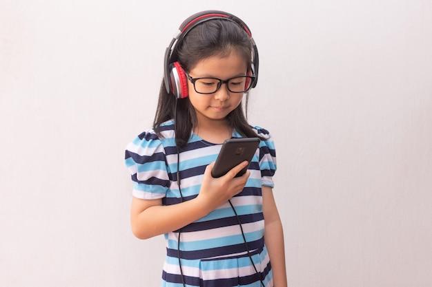 Menina da ásia com fones de ouvido, ouvindo música