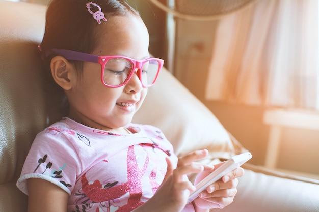 Menina da criança de ásia que joga o smartphone com feliz e sorriso em casa. foco seletivo e estilo hi-key.