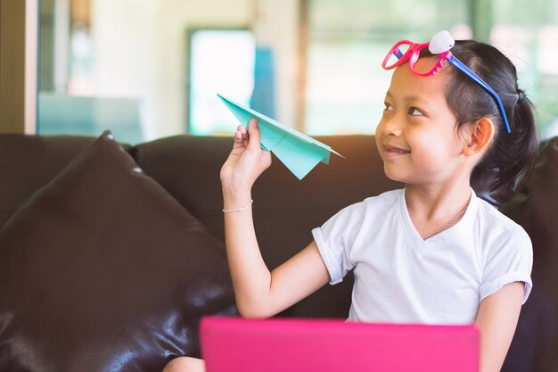 Menina da criança do sorriso que guarda o papel do avião com o computador para criativo em casa.