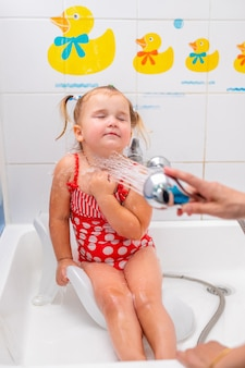 Menina da criança em um maiô vermelho toma banho antes de ir para a piscina.