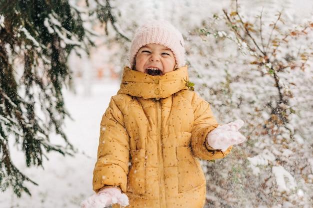Menina da criança feliz com o dia de neve no inverno. brincando ao ar livre no feriado de natal