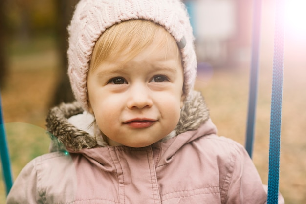Menina da criança iluminada pelo sol em malha chapéu olhando para o futuro