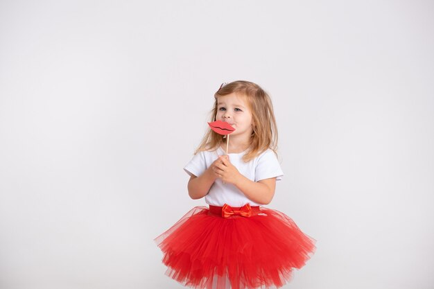 Menina da criança na saia vermelha detém os toppers ou design de lábios de adesivos em uma parede branca.
