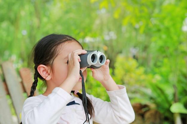 Menina da criança pequena em um campo que olha através dos binóculos na natureza ao ar livre.