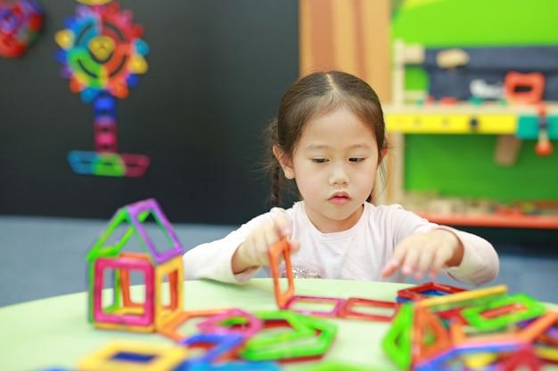 Menina da criança pequena que joga o brinquedo dos ímãs para o desenvolvimento do cérebro.