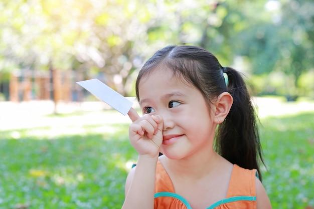 Menina da criança pequena que mostra um foguete do livro branco em seu dedo indicador no parque natural.