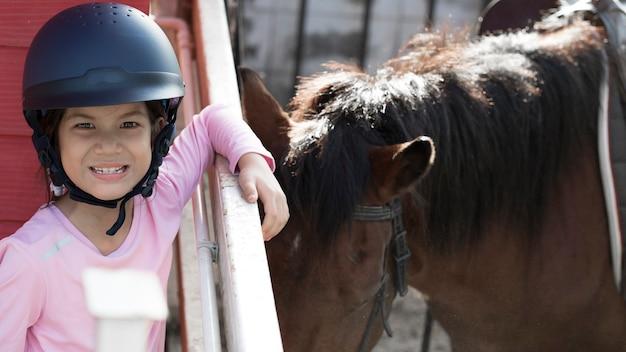 Menina da escola asiática com cavalo, cavalgando ou praticando passeios a cavalo no rancho de cavalos.