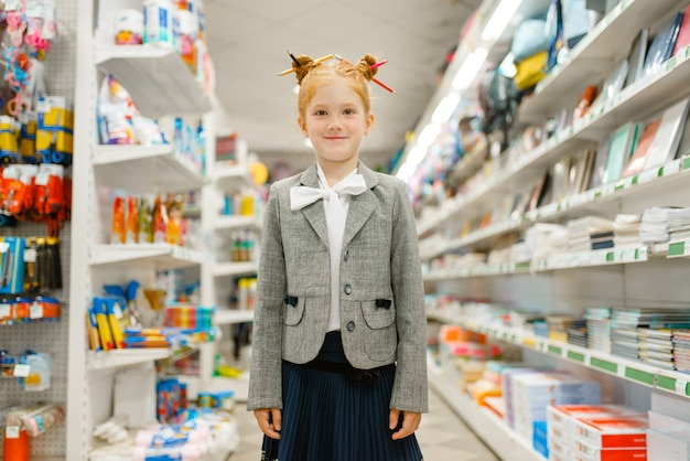 Menina da escola com cadernos em papelaria. criança do sexo feminino comprando material de escritório na loja, estudante no supermercado