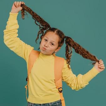 Menina da escola com camisa amarela brincando