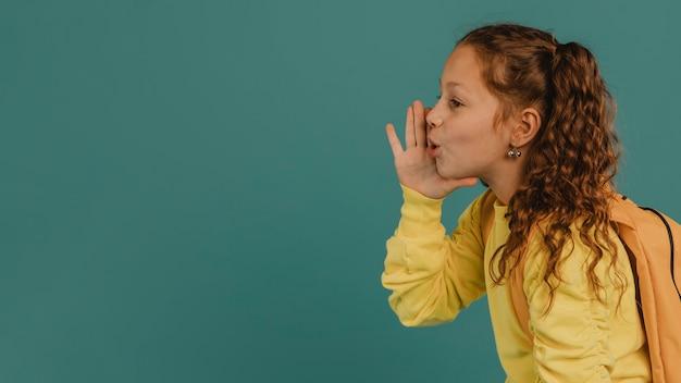 Menina da escola com camisa amarela contando um segredo