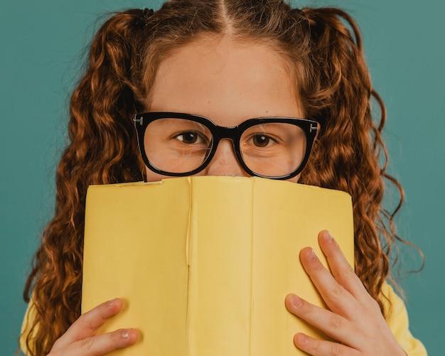 Menina da escola com camisa amarela segurando um livro