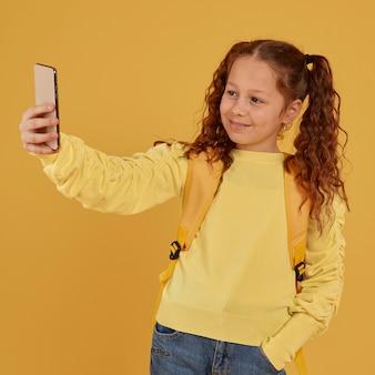 Menina da escola com camisa amarela tirando uma foto de si mesma