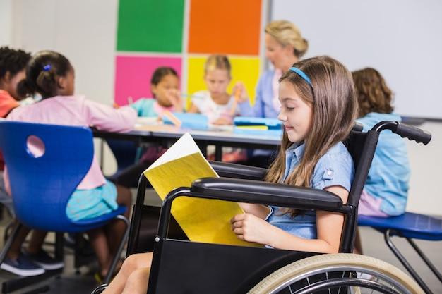Menina da escola com deficiência em cadeira de rodas, lendo um livro na sala de aula