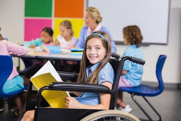 Menina da escola com deficiência em cadeira de rodas, segurando um livro na sala de aula