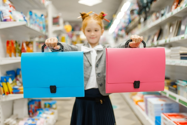 Menina da escola com duas pastas na papelaria. criança do sexo feminino comprando material de escritório na loja, estudante no supermercado