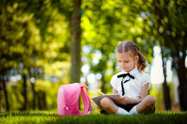 Menina da escola com mochila rosa sentado na grama depois da lição