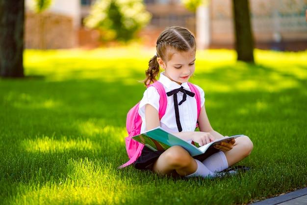 Menina da escola com mochila rosa sentado na grama depois das aulas e ler livro ou estudar lições,